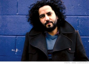 Daniel Bejar Destroyer wearing coat against blue wall