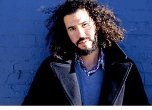 Daniel Bejar Destroyer wearing coat against blue wall