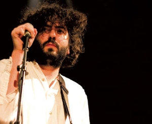 Daniel Bejar Destroyer performing with microphone and white shirt