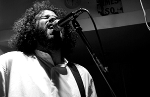 Daniel Bejar of Destroyer singing into microphone black and white