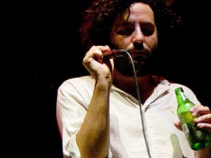 Daniel Bejar of Destroyer singing with microphone and beer