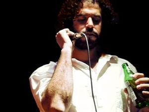 Daniel Bejar of Destroyer singing with microphone and beer
