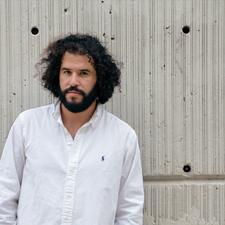 Daniel Bejar Destroyer wearing white shirt against concrete wall