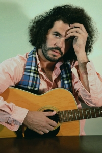 Daniel Bejar Destroyer in pink shirt and plaid scarf holding guitar against green background