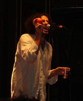 Daniel Bejar Destroyer wearing white shirt singing into microphone while shaking orange