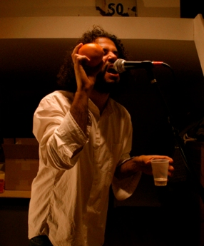 Daniel Bejar Destroyer wearing white shirt singing into microphone while shaking orange googleganger