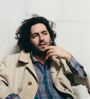 Daniel Bejar Destroyer hand on face wearing tan trench coat and plaid shirt on white wall.