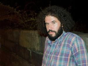 Daniel Bejar Destroyer plaid shirt against brick wall at night googleganger.