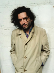 Daniel Bejar Destroyer leaning against white wall in a trenchcoat