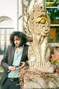 Daniel Bejar Destroyer holding sunglasses against a lion statue with a banana peel in it's mouth.